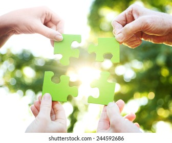 Hands holding up a green jigsaw puzzle against the sunlight