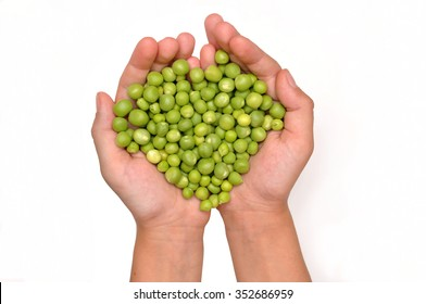 Hands holding green peas, in the shape of a heart isolated on white background. Fresh green peas in the children's hands. Green peas in his hands. A girl holds green peas.