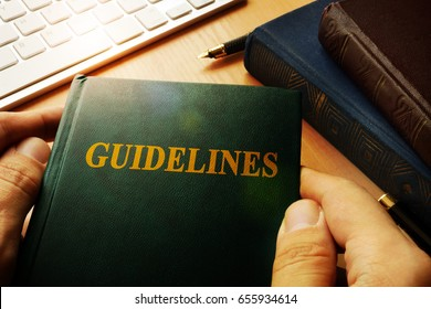 Hands holding Guidelines in an office.