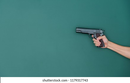 Hands holding gun in front of chalkboard.