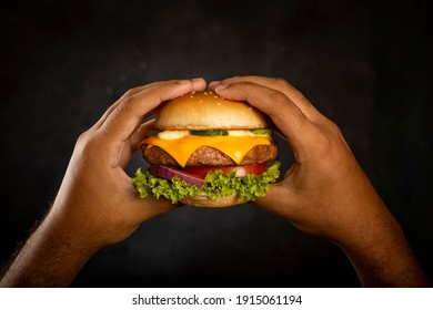 Hands holding hamburger on dark background.