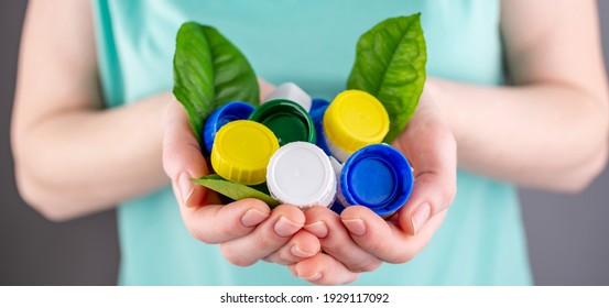 Hands are holding a handful of colorful plastic lids with green leaves. Concept of environmental pollution, eco friendly behavior, waste sorting and plastic recycling.