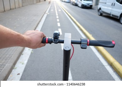 Hands holding handlebar of a electric scooter