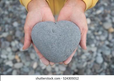 hands holding heart - heart shaped stone