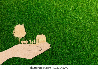 hands holding home family car and tree of grass background paper cut
