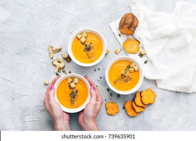 Hands holding homemade fresh sweet potato soup