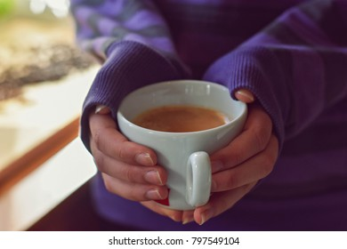 hands holding hot cup in morning sunlight
