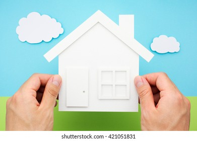 Hands holding house against sky and grass field made of paper. House shaped paper cutout on paper background.