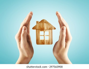 hands holding house on a blue background