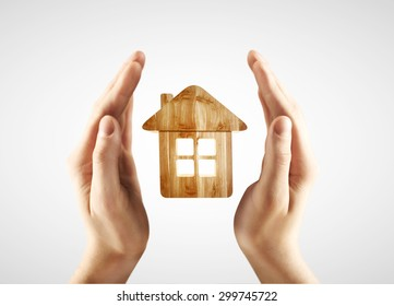 hands holding house on a white background