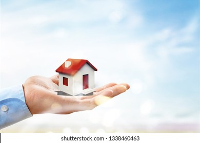 hands holding house. Real estate and property