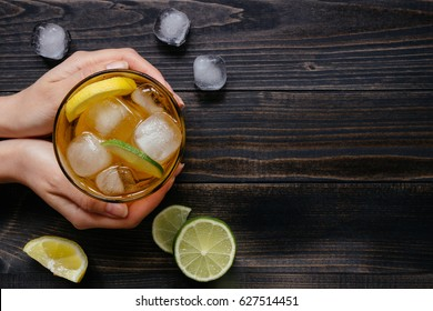 Hands holding ice drink with lemon and lime on the wooden table, top view. With copy space.