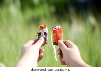 A hands holding Japanese amulets (Japanese on the amulet is mean a good relationship with your lover ). Amulet for a lover for their relationship.