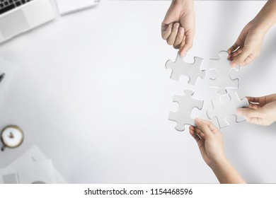 Hands holding jigsaw puzzle on white office desk table top view with copy space for teamwork concept