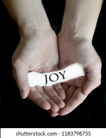 Hands holding joy word sign on paper illustrating choosing to be happy