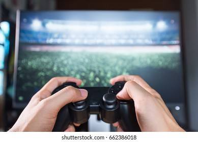 Hands Holding a Joystick Controller while playing a video games at home