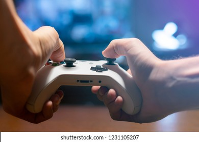 hands holding a joystick and play video games at home in the night