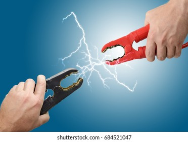 Hands holding jump start connectors with sparks between them