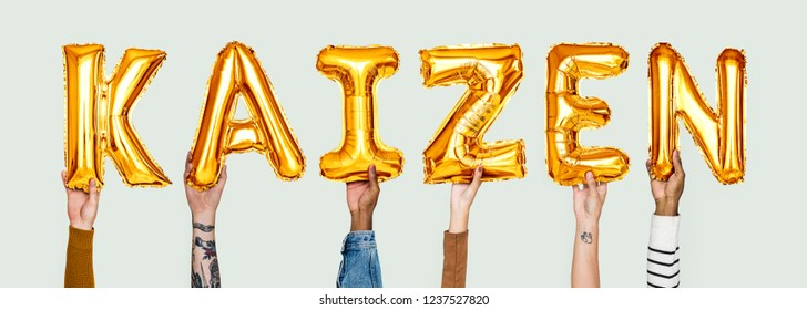 Hands holding Kaizen word in balloon letters