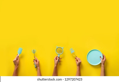 Hands holding kitchen tools holding kitchen tools, sieve, rolling pin, bowl, sieve, brush, whisk, spatula for baking and cooking on yellow background. Food frame, bake concept with copy space.