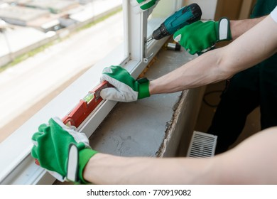 Hands holding a level tool. Construction workers are installing a window in a new house. Creating comfort for your home.