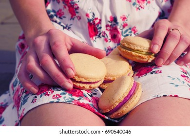 Hands holding macarons. Gentle woman hands holding sweet french desserts. Composition of sweet organic macarons in human hands. Girl showing macarons to the camera.Model in dress eating sweet dessert