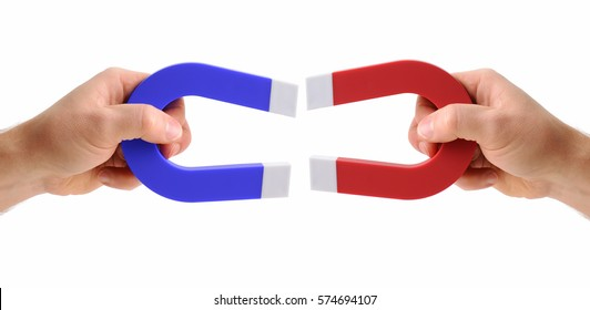 hands holding magnets one red and one blue isolated on a white background