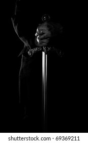 hands holding medieval sword on black background