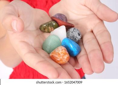 Hands holding a mixture of Gemstones