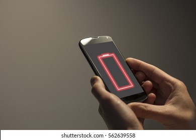 Hands holding mobile with low battery warning on the screen.