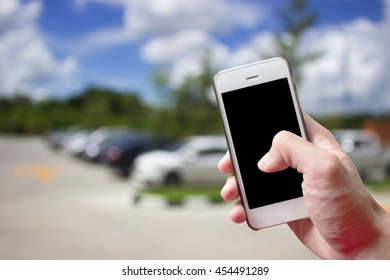 hands holding mobile phone with blur cars parking