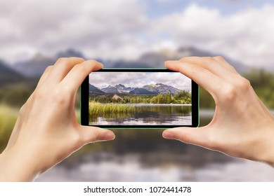 Hands holding a mobile phone. Photographing mountain landscapes using a smartphone.