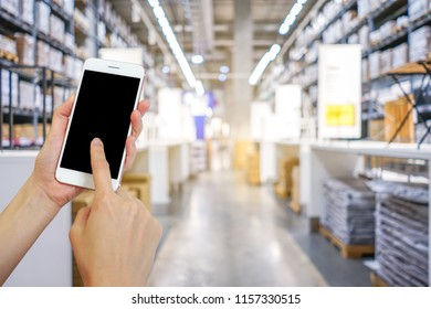 Hands holding mobile phone with shopping mall or department store  blurred background and bokeh light