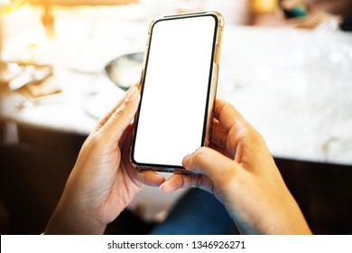 Hands holding mobile phone texting message