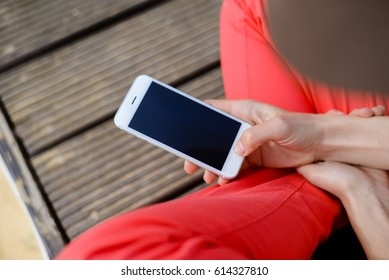 Hands holding mobile phone, wooden floor background. Person barefoot feeling relax, closeup image