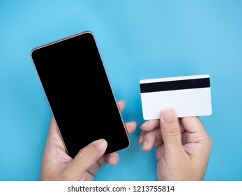 Hands holding mobile smart phone and credit card on blue isolated background. Internet and shopping online concept.