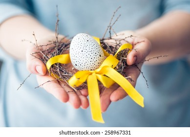 Hands holding modern painted easter egg in a small nest