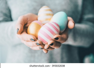 Hands holding modern painted easter eggs. Selective focus. Toned picture