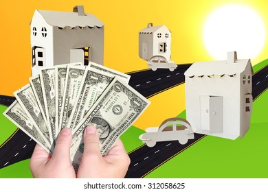 Hands holding money (American dollars) with symbolic cardboard houses, automobiles and new roads aspiring to sun shining in the background