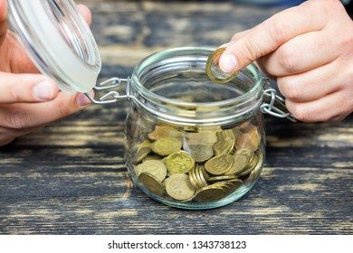 Hands holding money in a glass jar