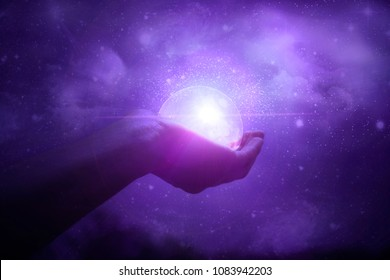 Hands holding the moon against the starry sky. Galaxy. Magic