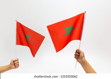 hands holding Moroccan Flags