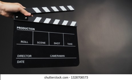Hand's holding movie slate  or Clapperboard use in video production ,film, cinema industry on black background.