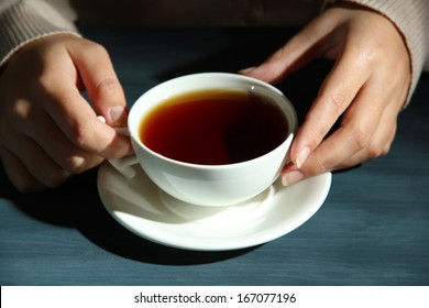 Hands holding mug of hot drink, close-up