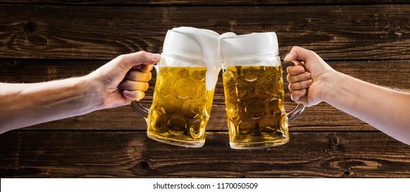Hands holding mugs of Bavarian beer Oktoberfest
