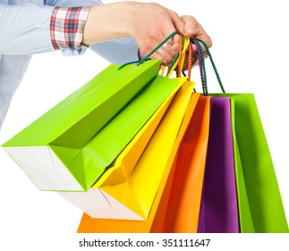 Hands holding multicolored paper bags isolated on white; shopping concept