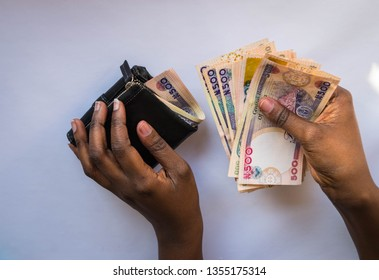 Hands holding Nigerian naira notes and leather wallet isolated on white background. Black African woman Counting or spend money. for personal finance and banking concept