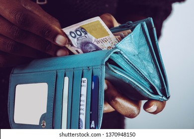 Hands holding Nigerian naira notes and leather wallet isolated on white background. Black African woman paying for items or spend money. for personal finance and banking concept