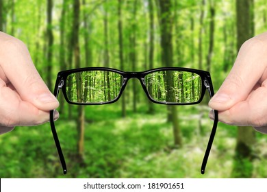 Hands holding and offering eye glasses to look at amazing green forest landndscape.Sharp as a good sight symbol and unsharp as a bad sight symbol