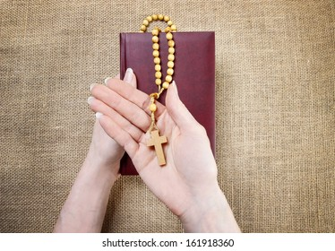 Hands holding old Holy Bible and wooden brown rosary. Hessian background.
